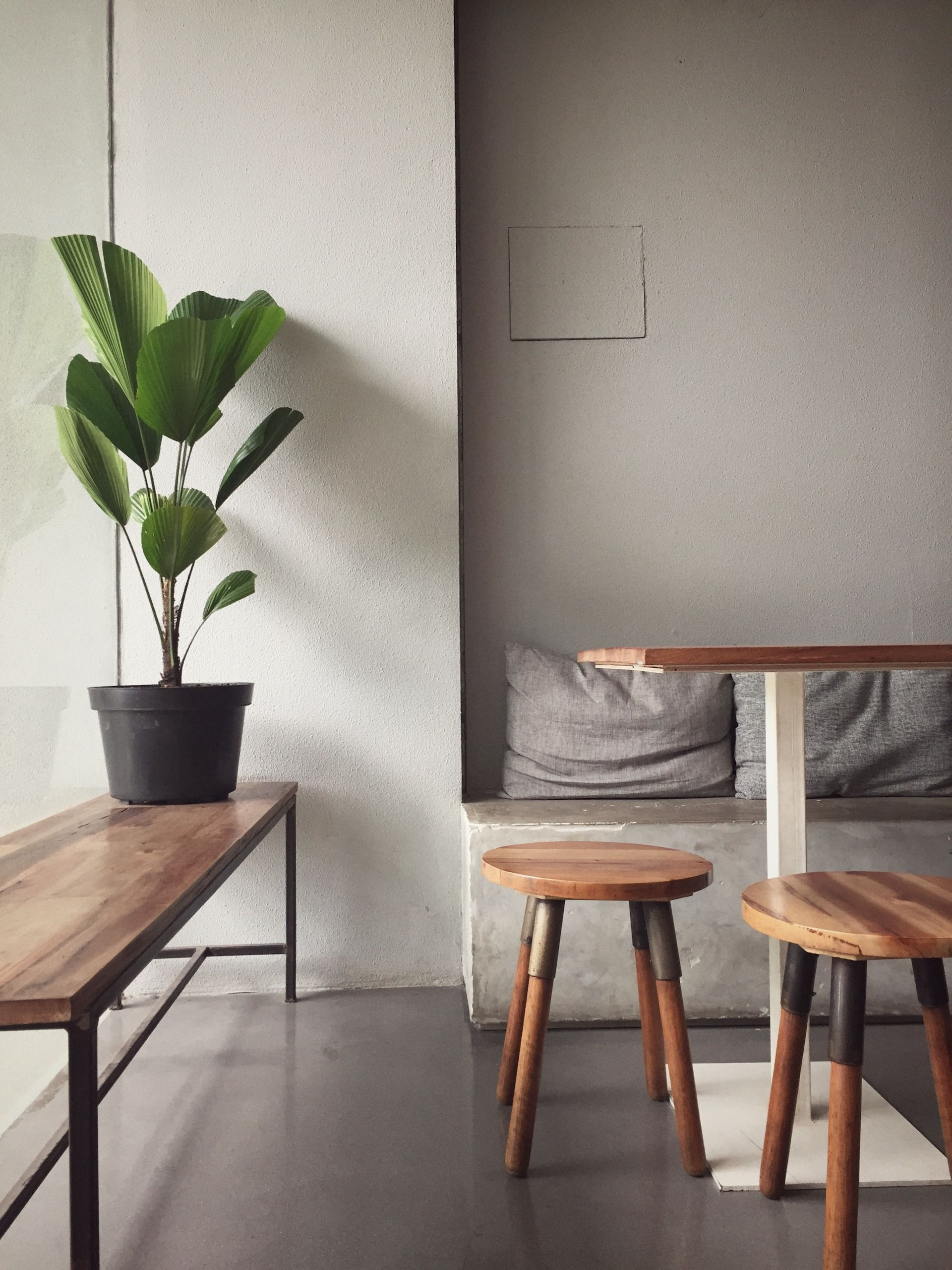 A cozy, empty sitting space that has wooden furniture to eat at or to just sit comfortably by the window.