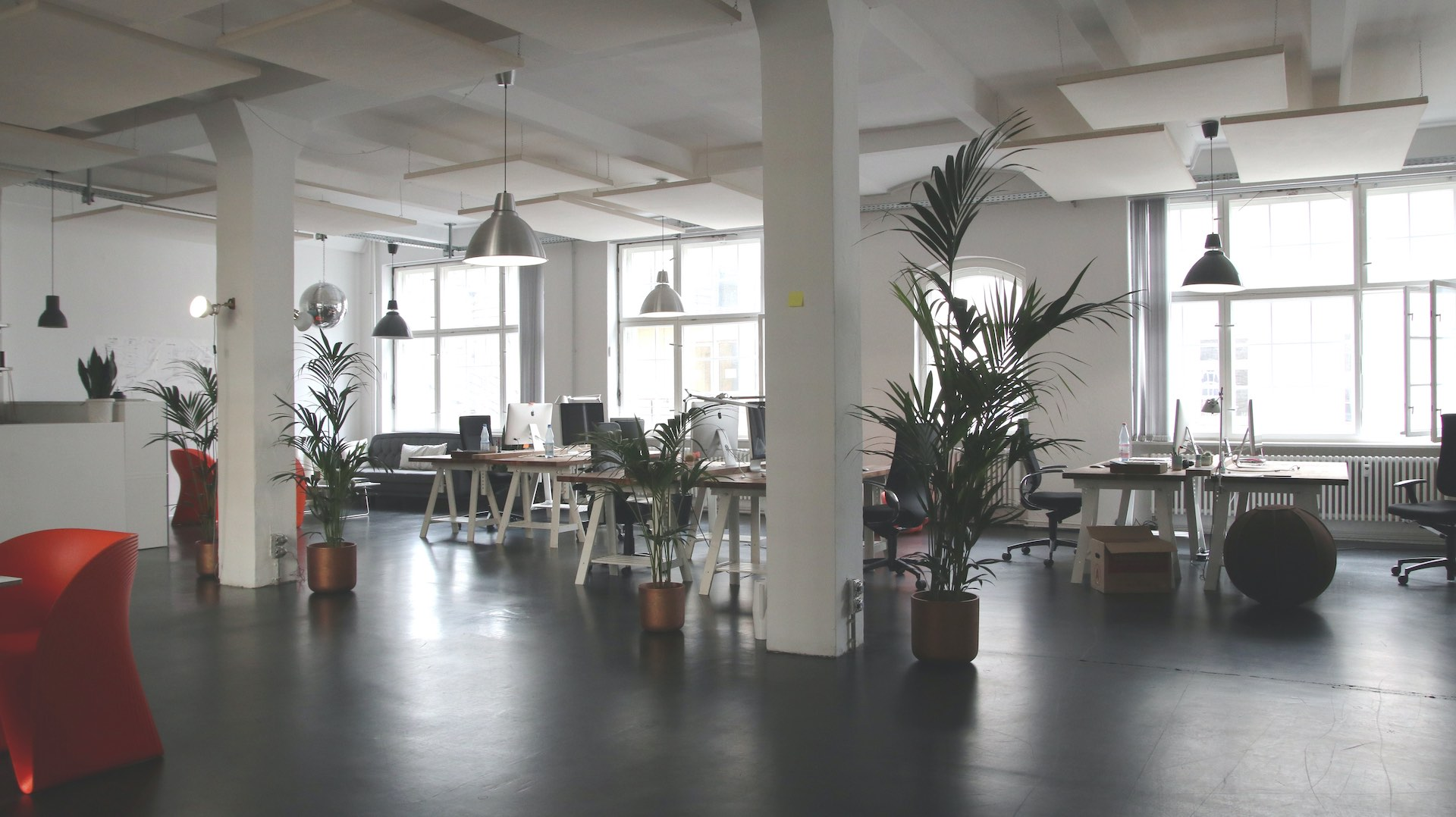 A beautiful open office with lots of natural light and green plants. There are desks that look like drafting tables and a sitting area for scrum meetings in the corner.