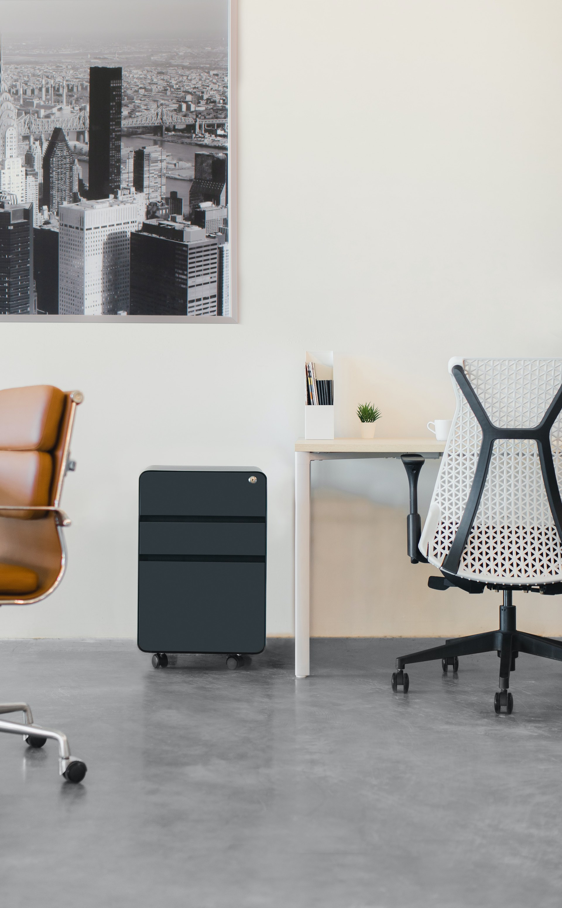 An extremely modern personal workspace. There are concrete floors and high-end office furniture with leather and wood.