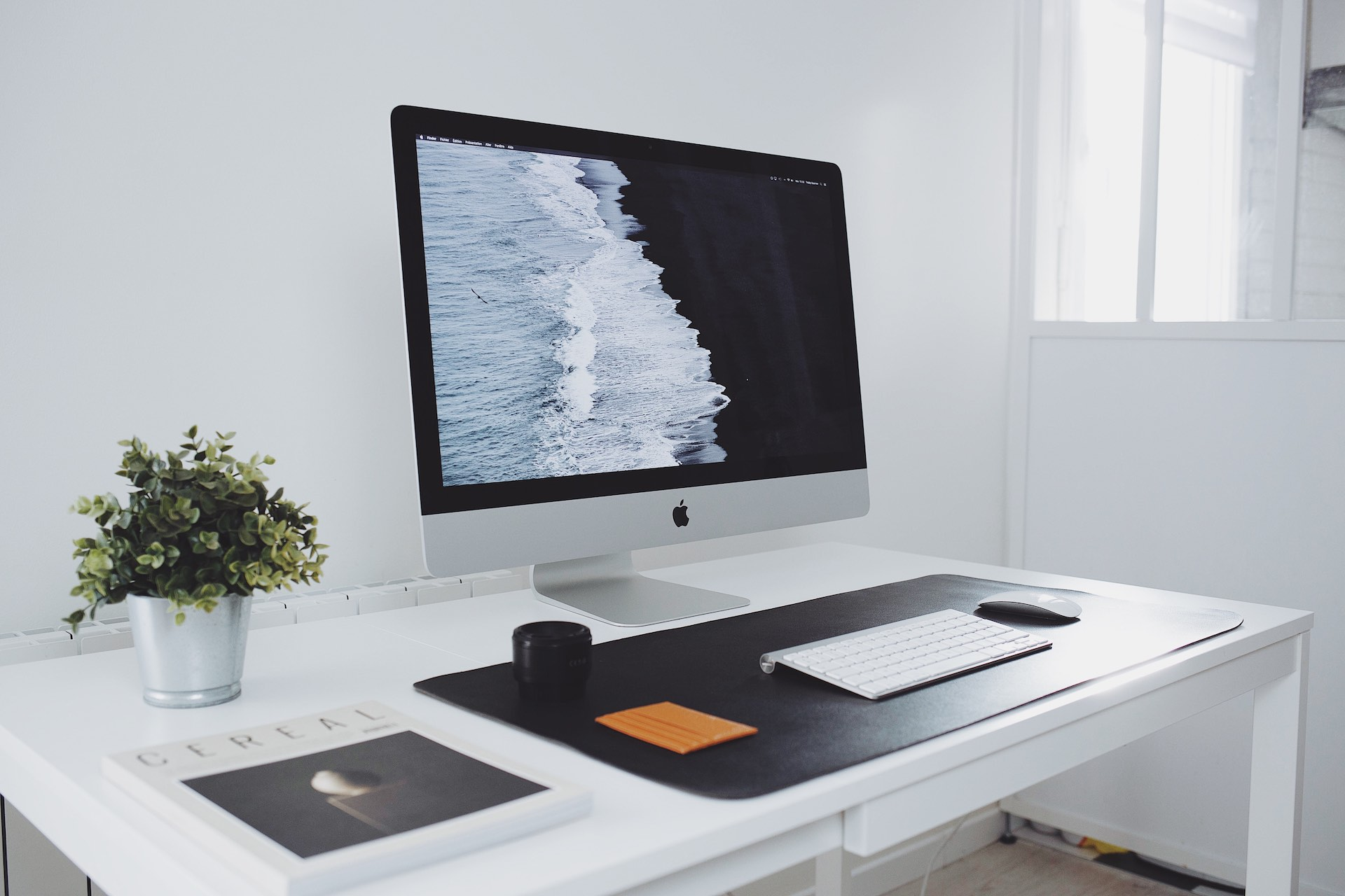 A very clean, modern work space with an iMac on a desk. The entire space is white, including the desk. All the items on the desk are placed symmetrically.