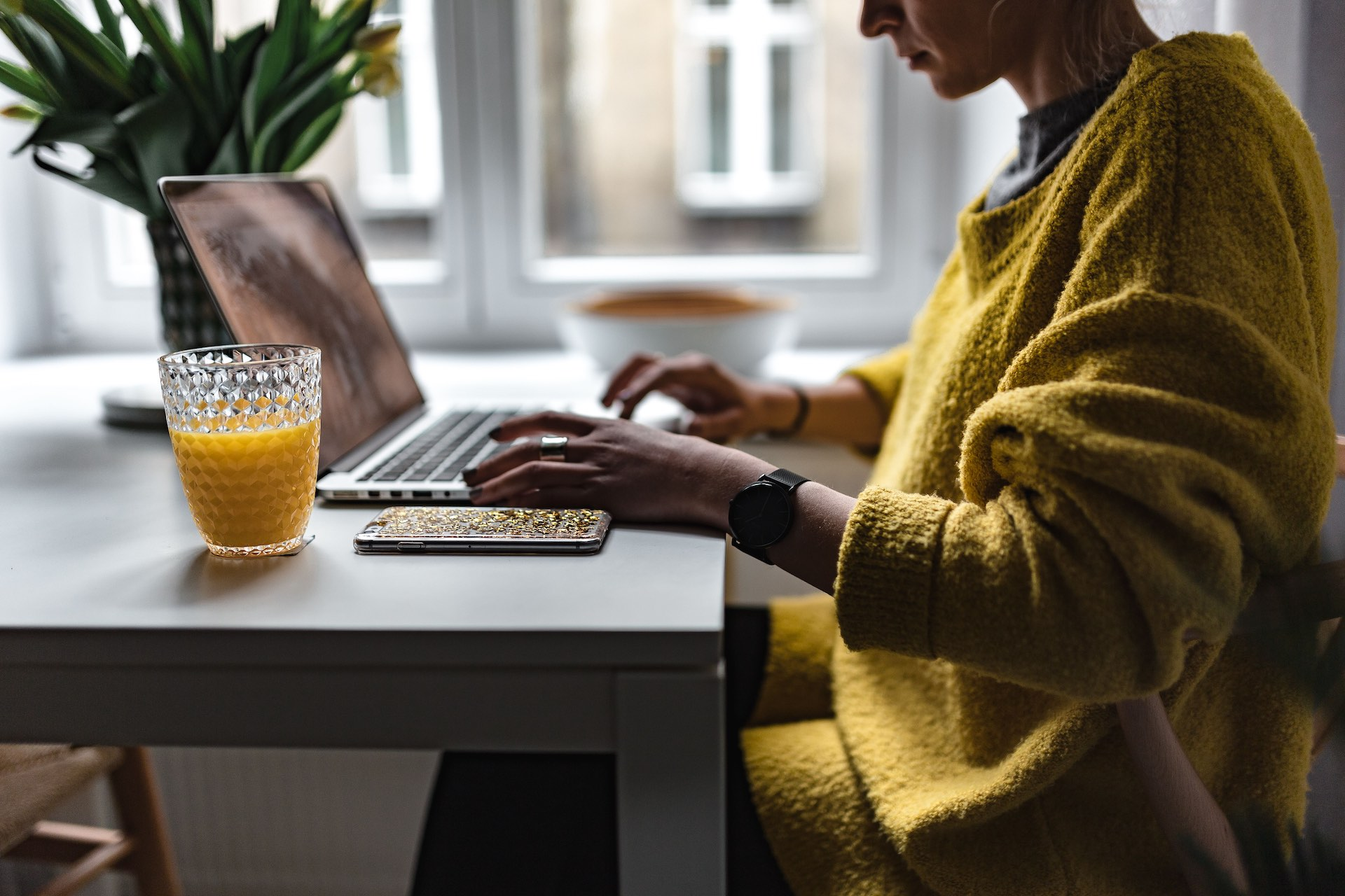 A woman working on her resume / CV in the morning while she eats breakfast and drinks orange juice at the same time. She's sitting at a modern table in front of a window with green plants.