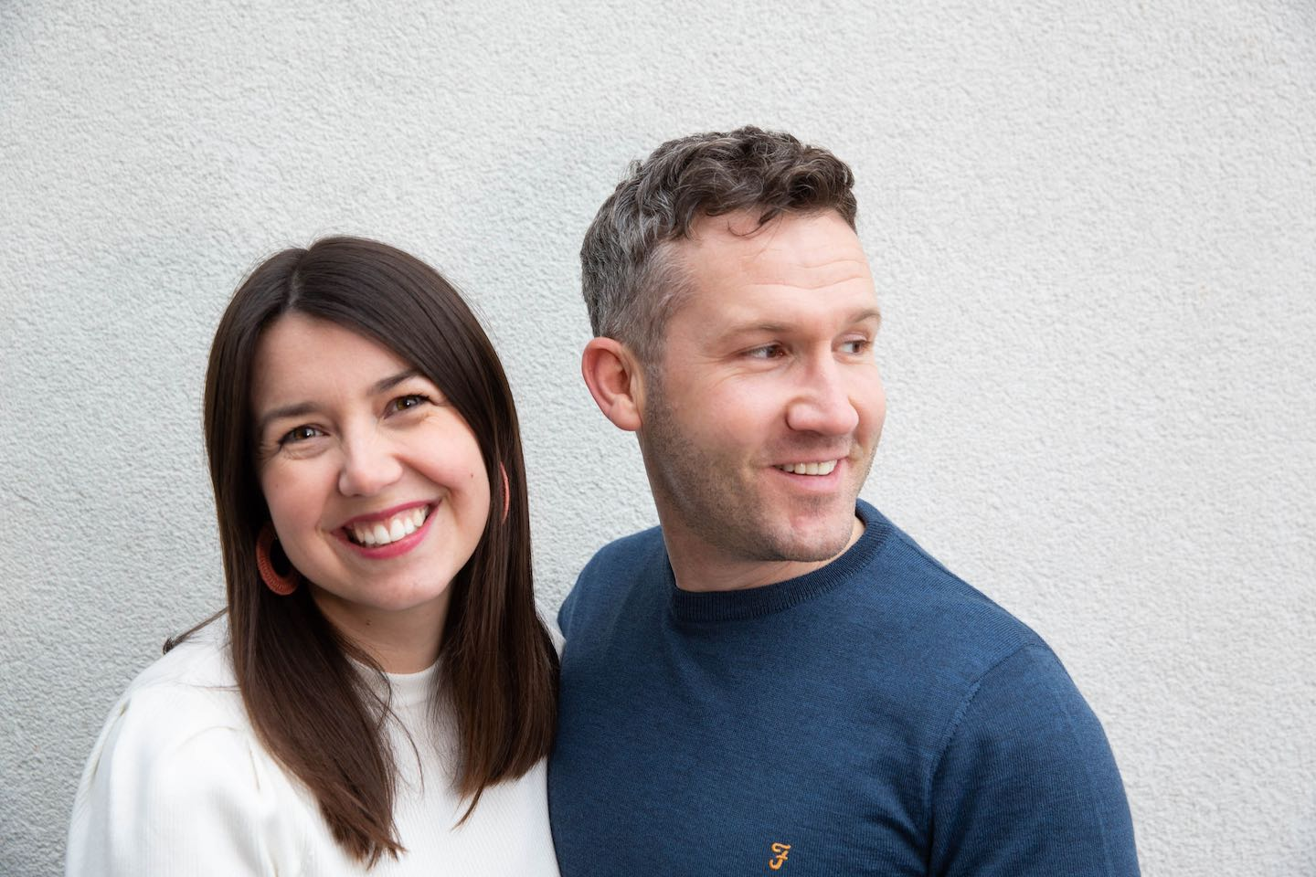 A picture of Joel & Hannah, owners of The English Meeting Room standing close together against a white wall.