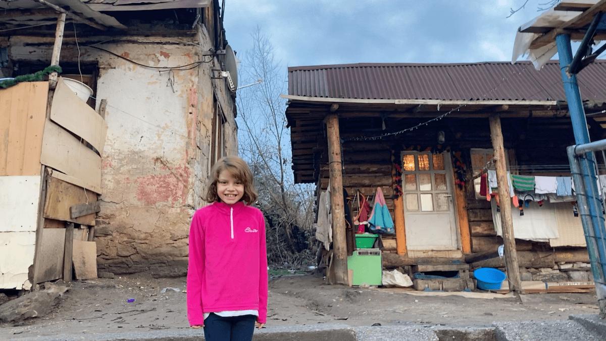 Dívka v romské osadě před chatrčí svých rodičů