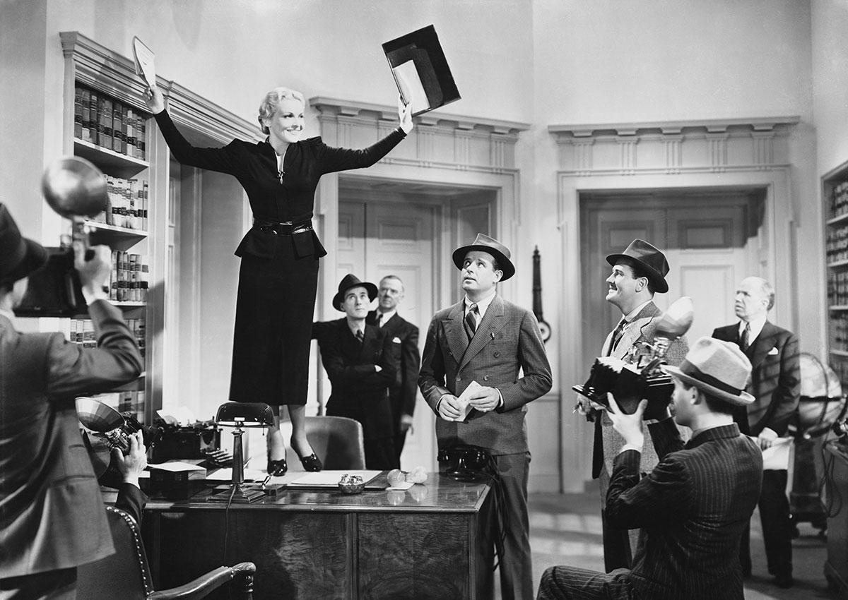 Photo vintage business femme tenant un discours debout sur un bureau entourée d'hommes