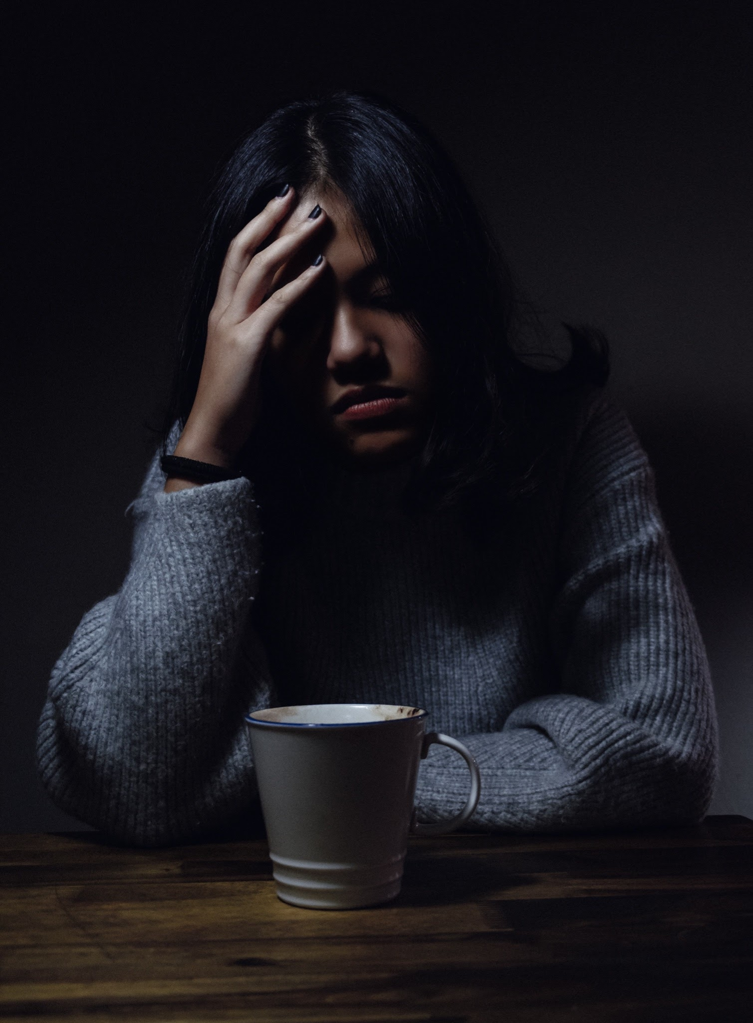 Stressed women leaning over coffee cup