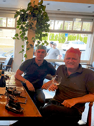 Two blokes enjoying a glass of wine at Christmas party