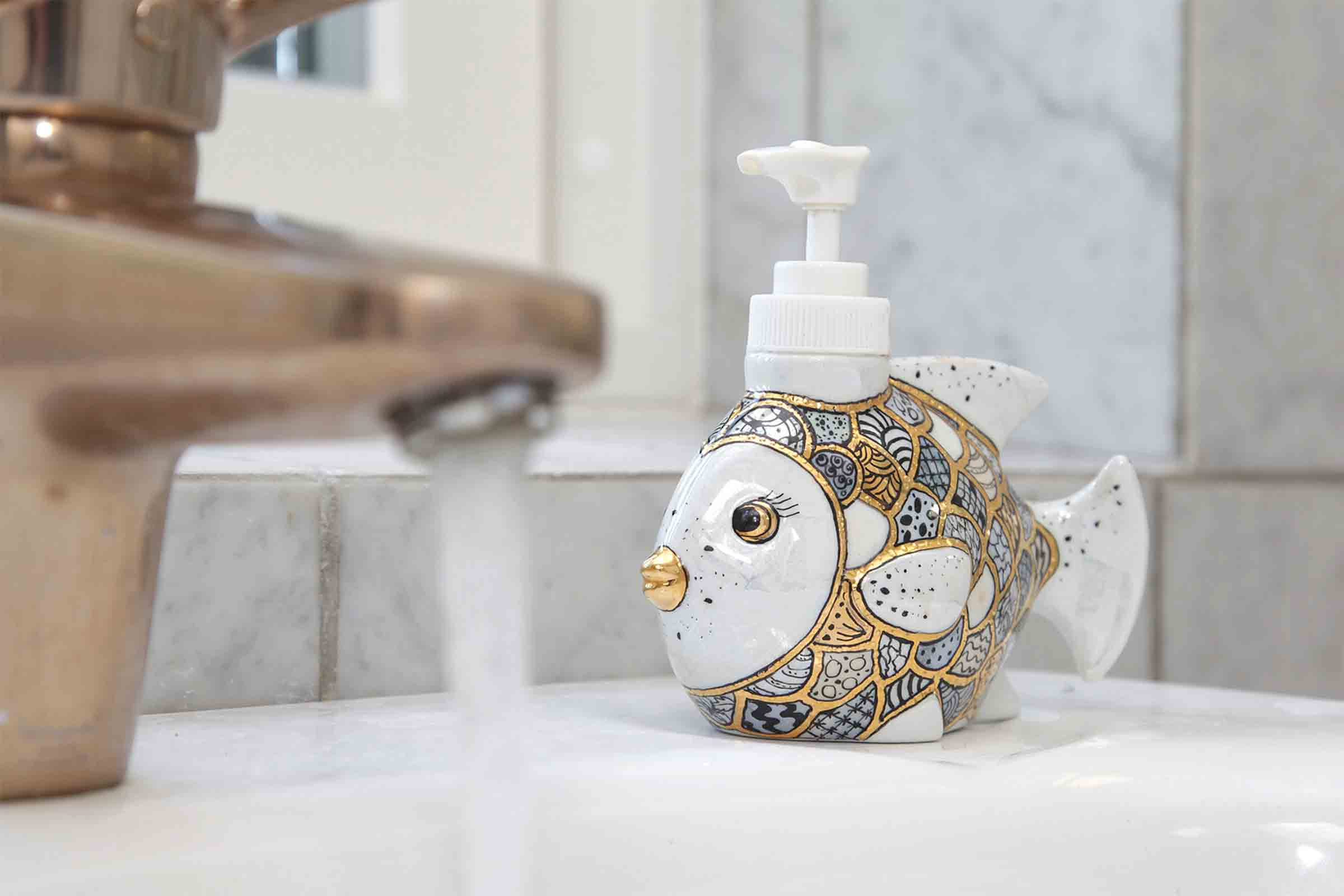 Running tap water and fish soap dispenser