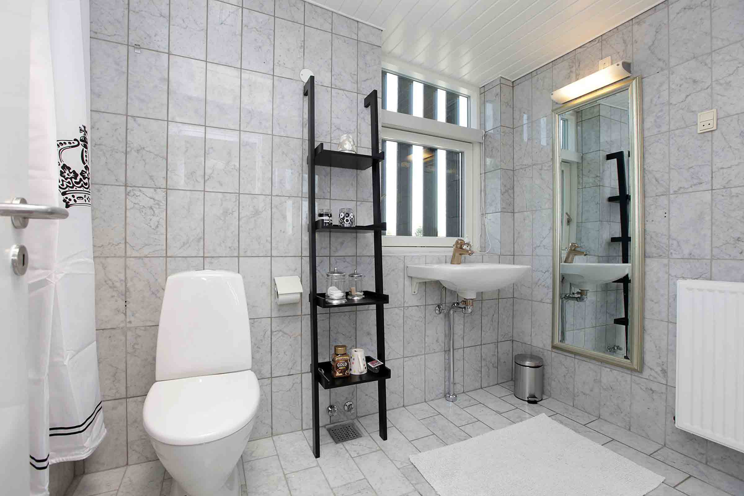 Shared bathroom with toiletries, sink, and toilet bowl