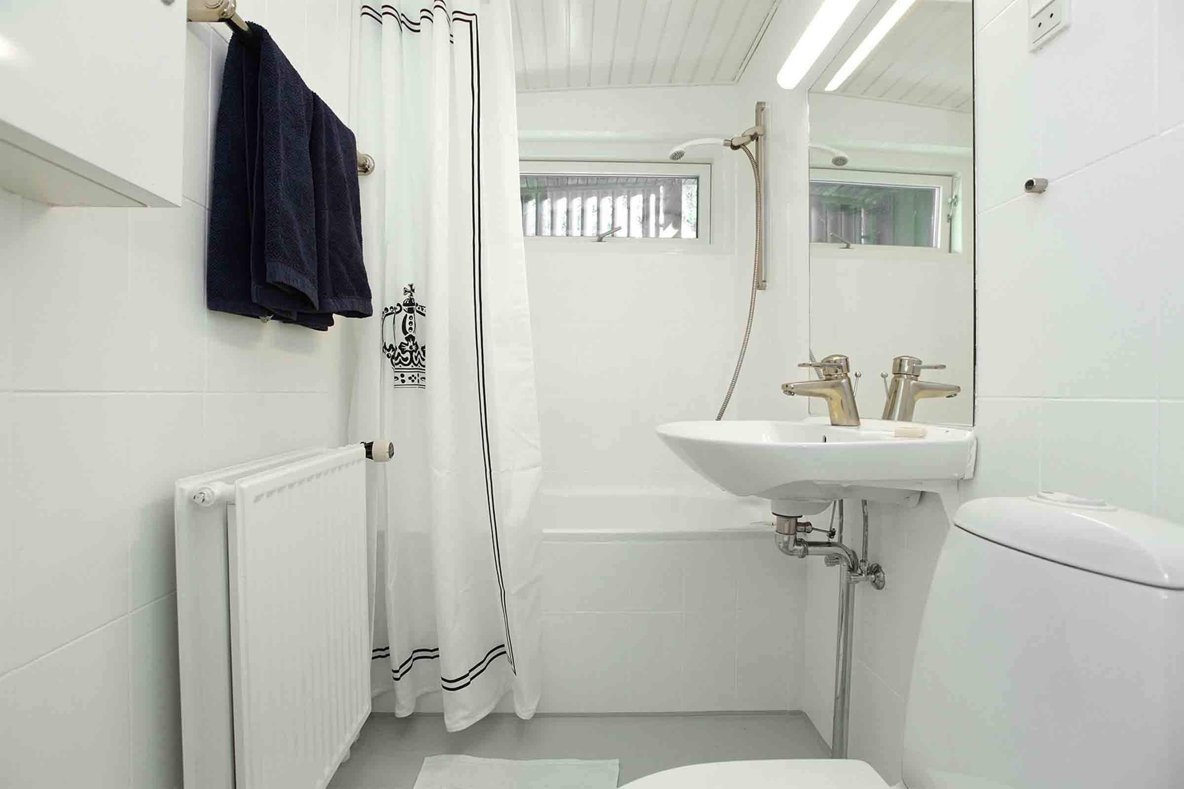 Private bathroom with toiletries, sink, bathtub, heater and toilet bowl