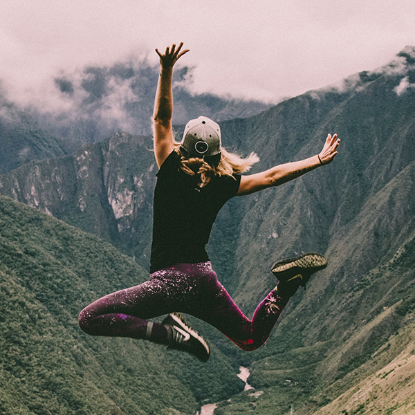 A person jumps in front of mountains