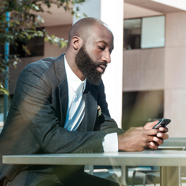 A man looks pensively at his phone