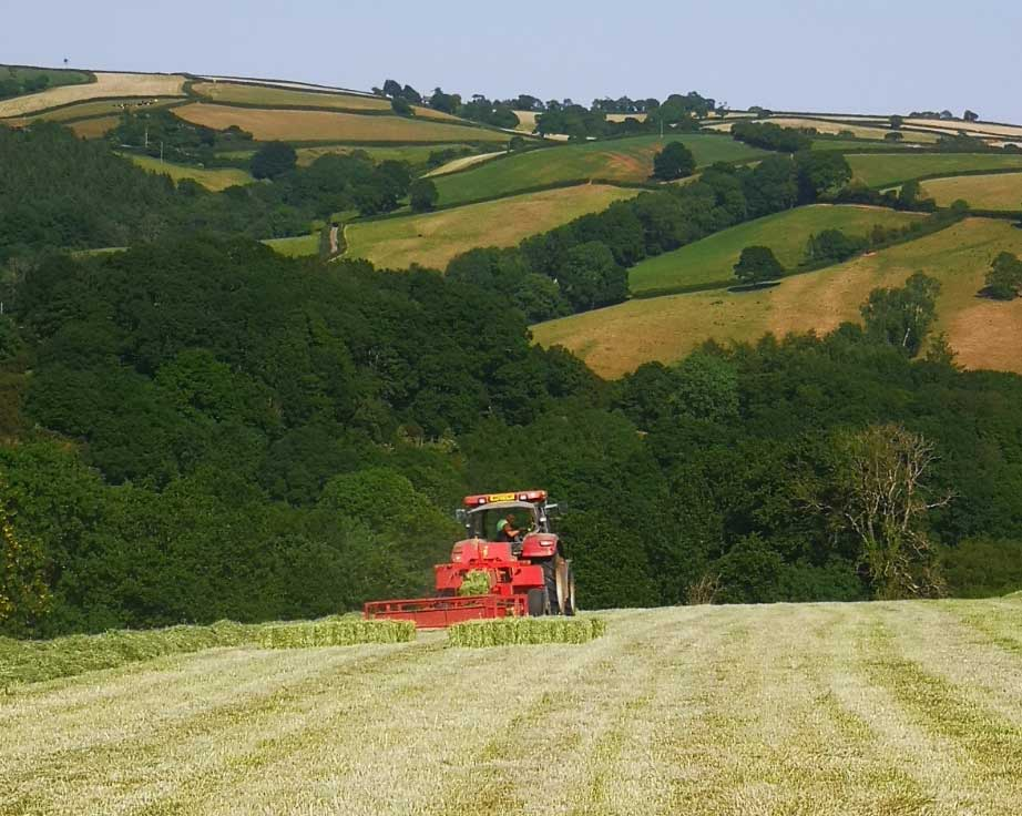 A red tractor harvesting within the rolling hills of the Devonshire countryside.