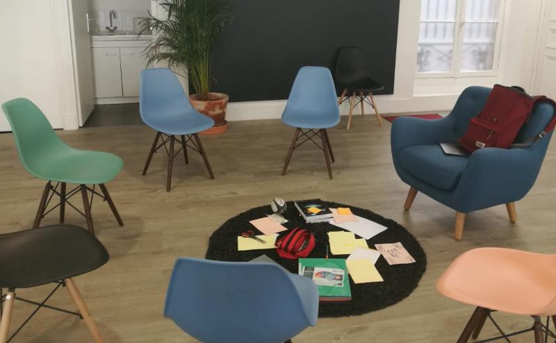 Un cercle de chaises vides avec du materiel au centre (stylo, post-it, feutres, trousse). Photo prise lors d'un We Open Space