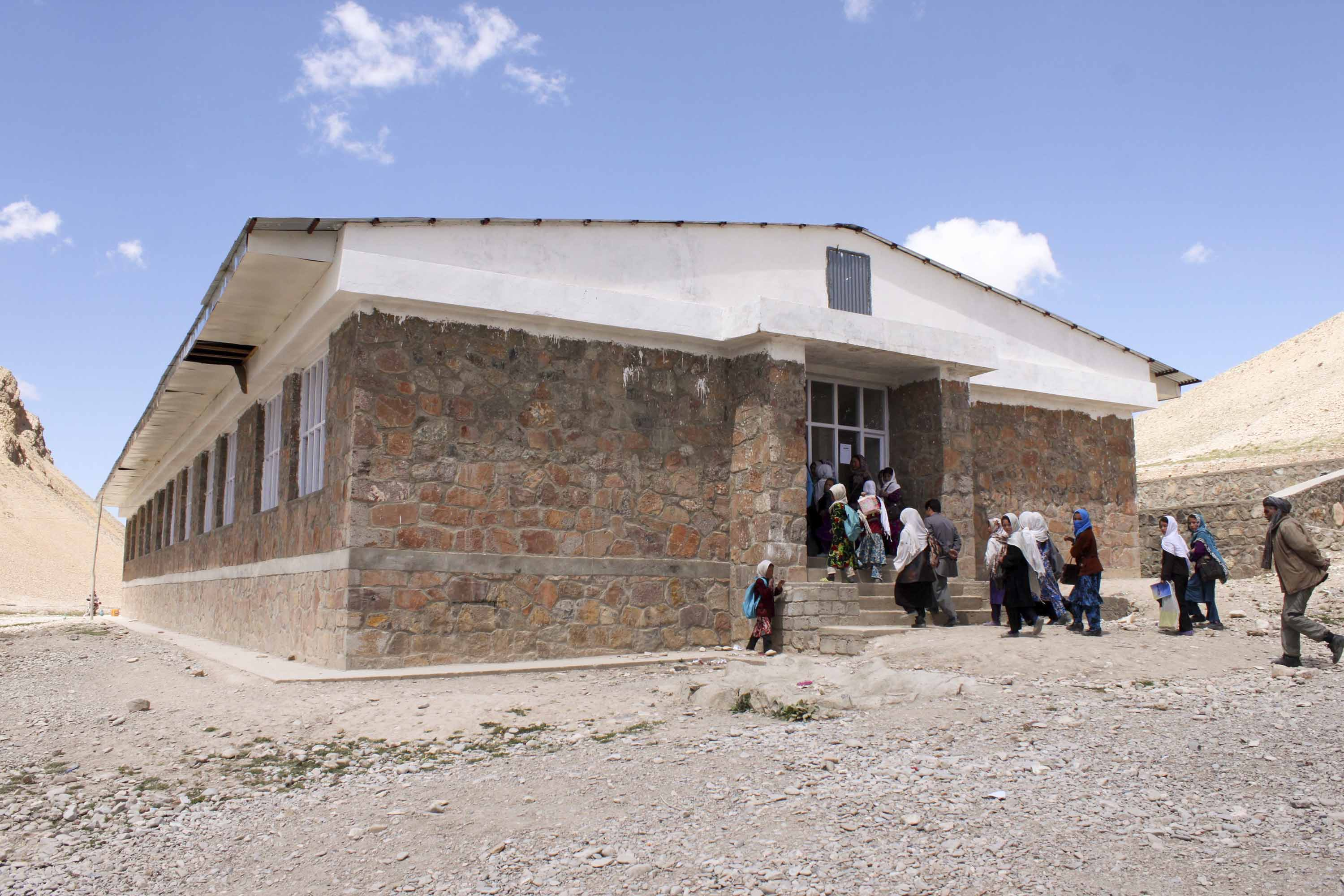 An image of a stone school building with children rushing into it.