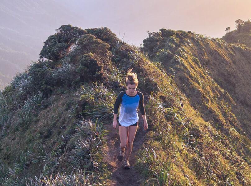 Frau erklimmt den Grat eines Berges.