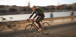 Mann auf Fahrrad fährt dynamisch über eine Brücke.