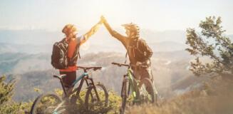 Fahrradfahrer geben sich einen High-Five auf dem Gipfel eines Berges.