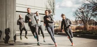 Eine Gruppe an Läufern laufen um die Hausecke.