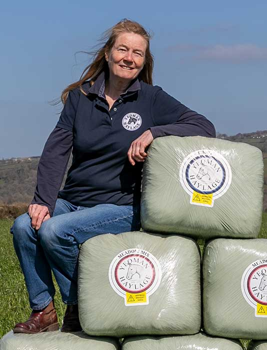 Woman casually sits on wrapped bales of Haylage