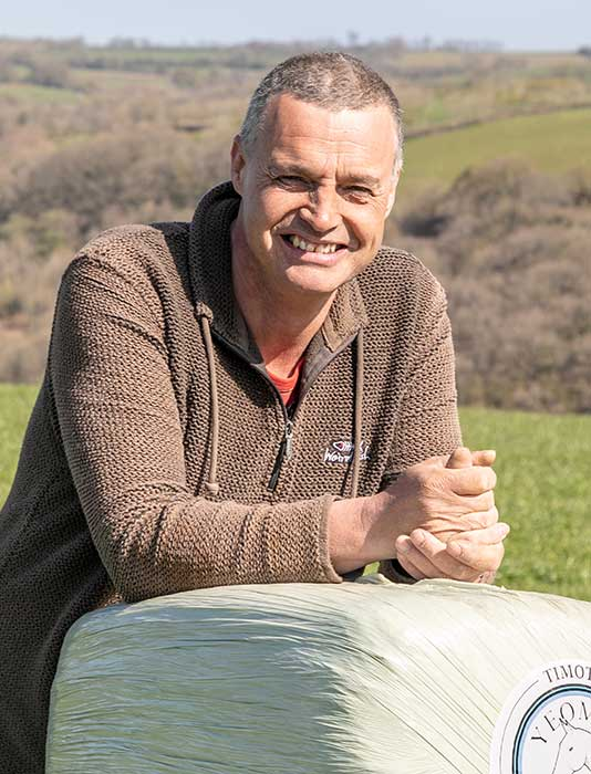 Man wearing a brown jumper leans on a bale of Haylage