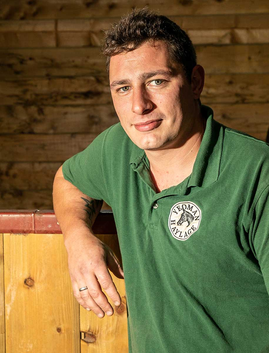 Man wearing green polo shirt casually leans on stable door