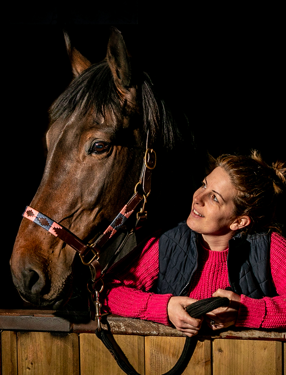 Woman looks admiringly at a horse within a stable.