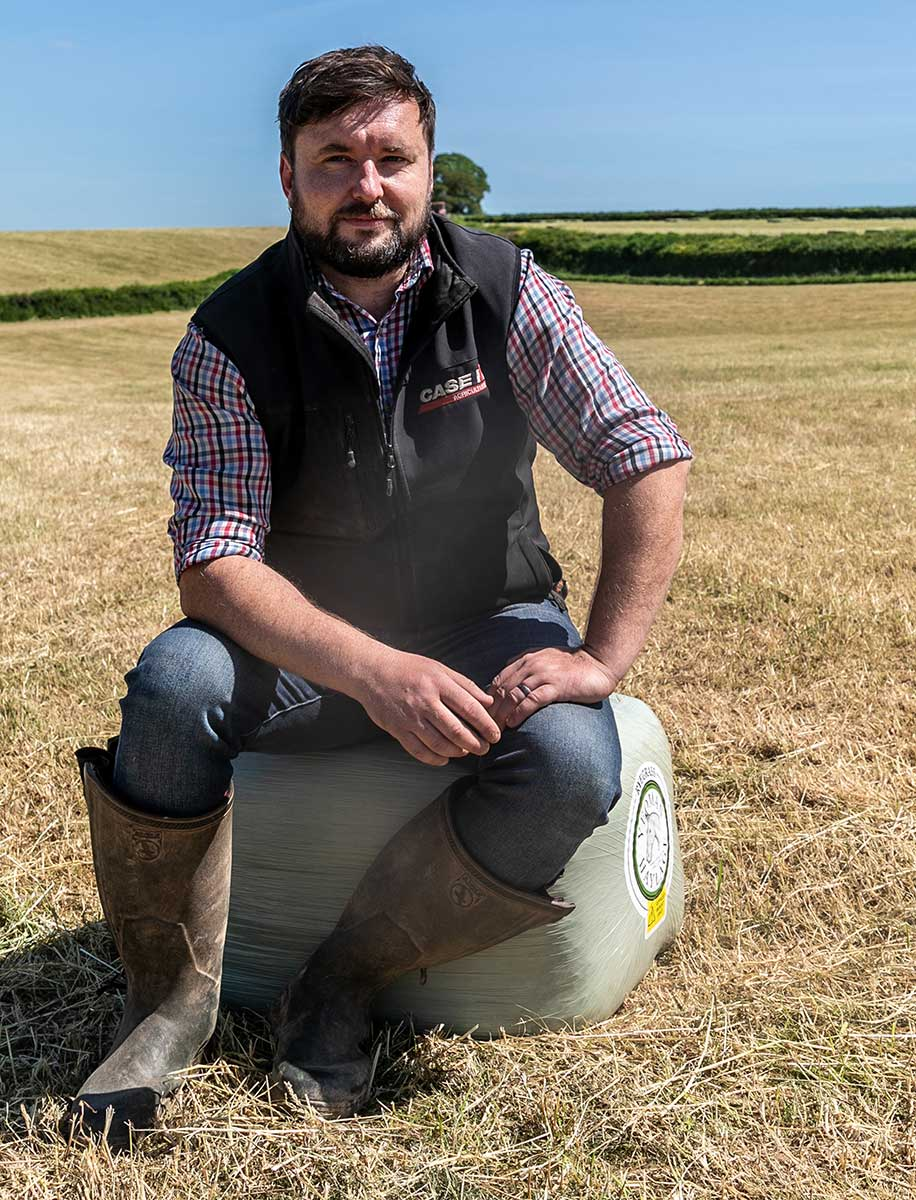 Farmer sits on wrapped haylage bale.