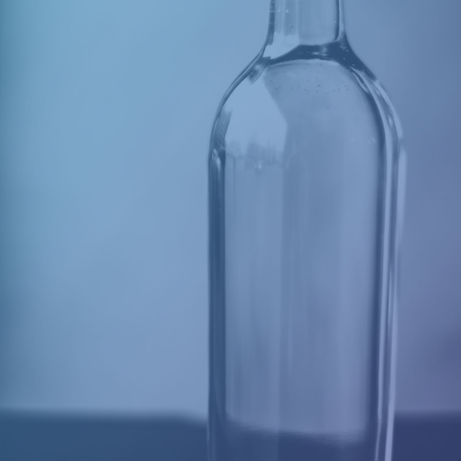 A clear glass bottle with a long neck containing a clear liquid