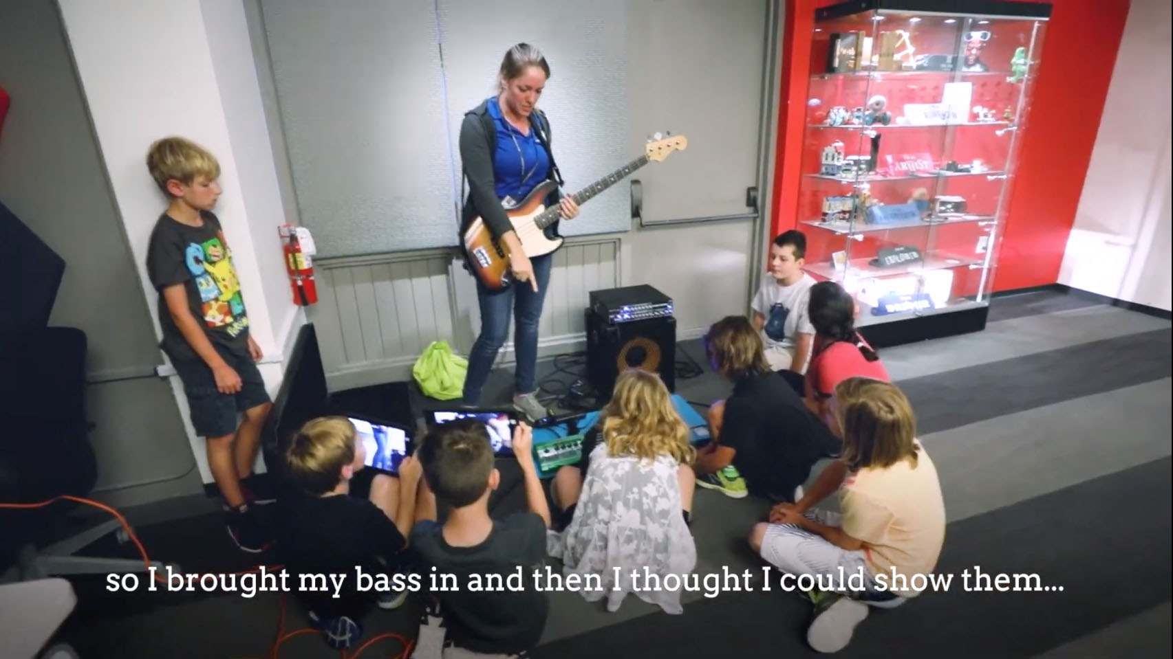 Natalie, camp facilitator, shows campers how different pedals effect the sound of a bass guitar