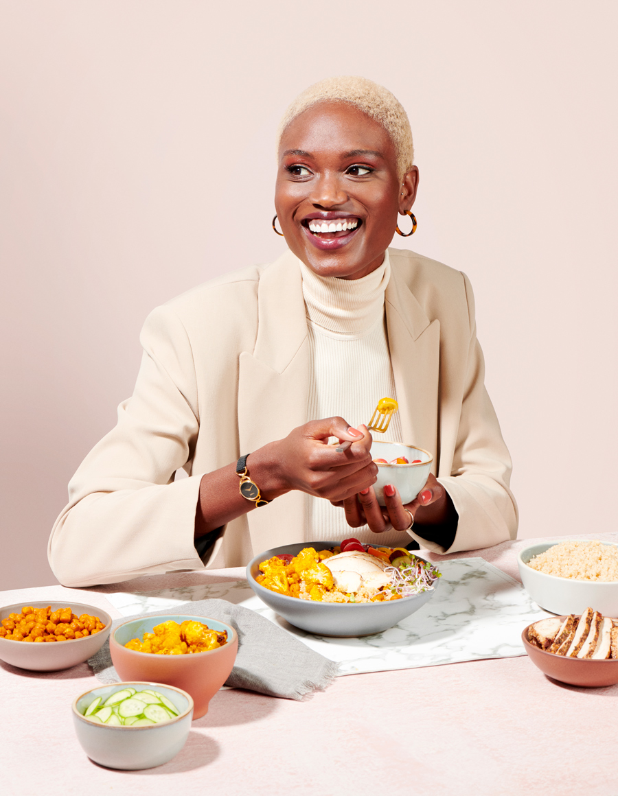 Woman sitting at a table with healthy dishes.