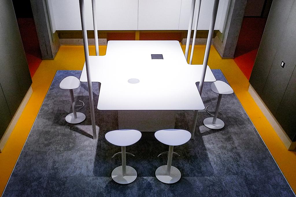 Blick auf den beleuchteten Tisch mit Hockern in der imba creative zone