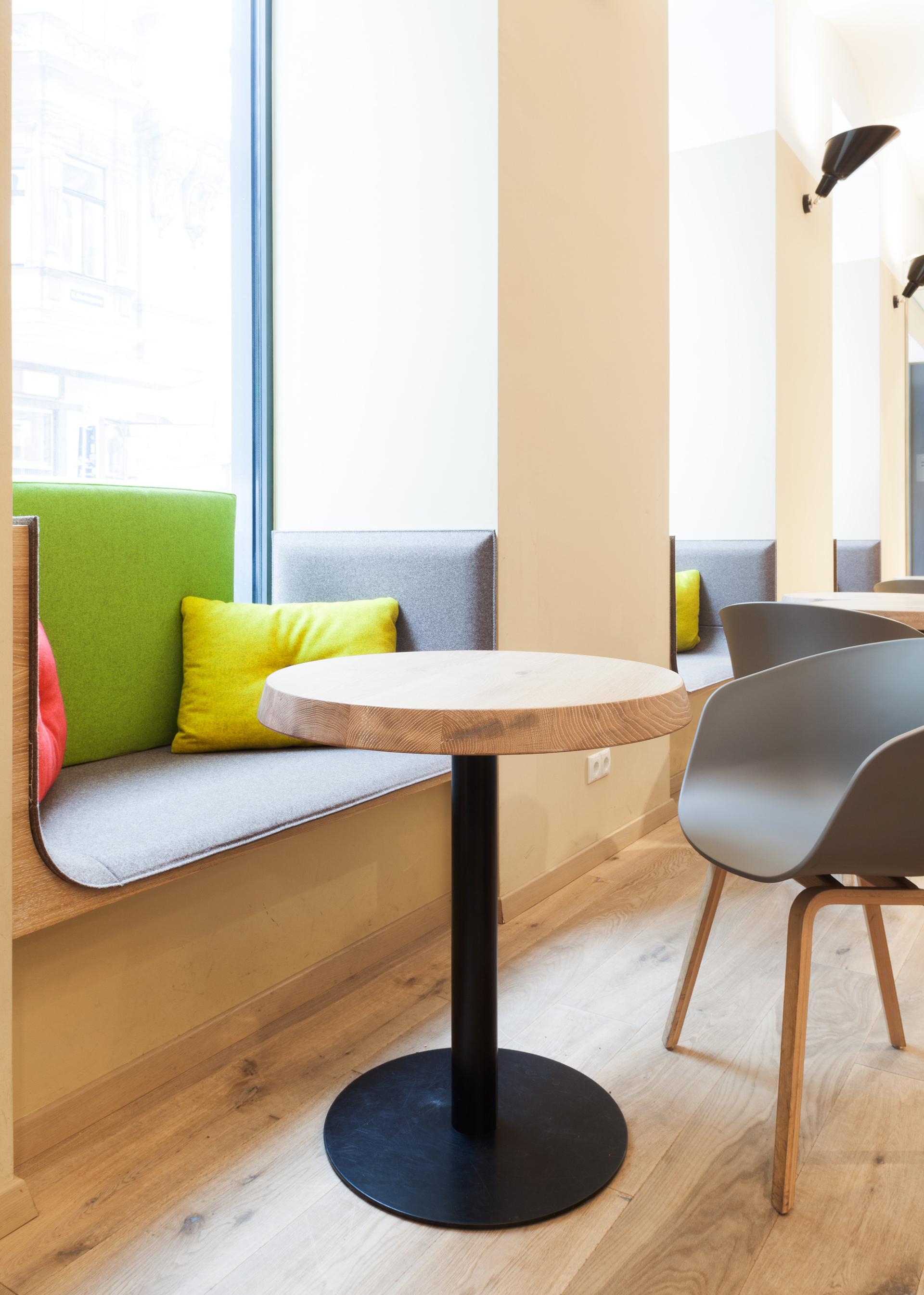 Detailansicht einer Sitzbank mit kleinem runden Tisch in der Rauch Juice Bar