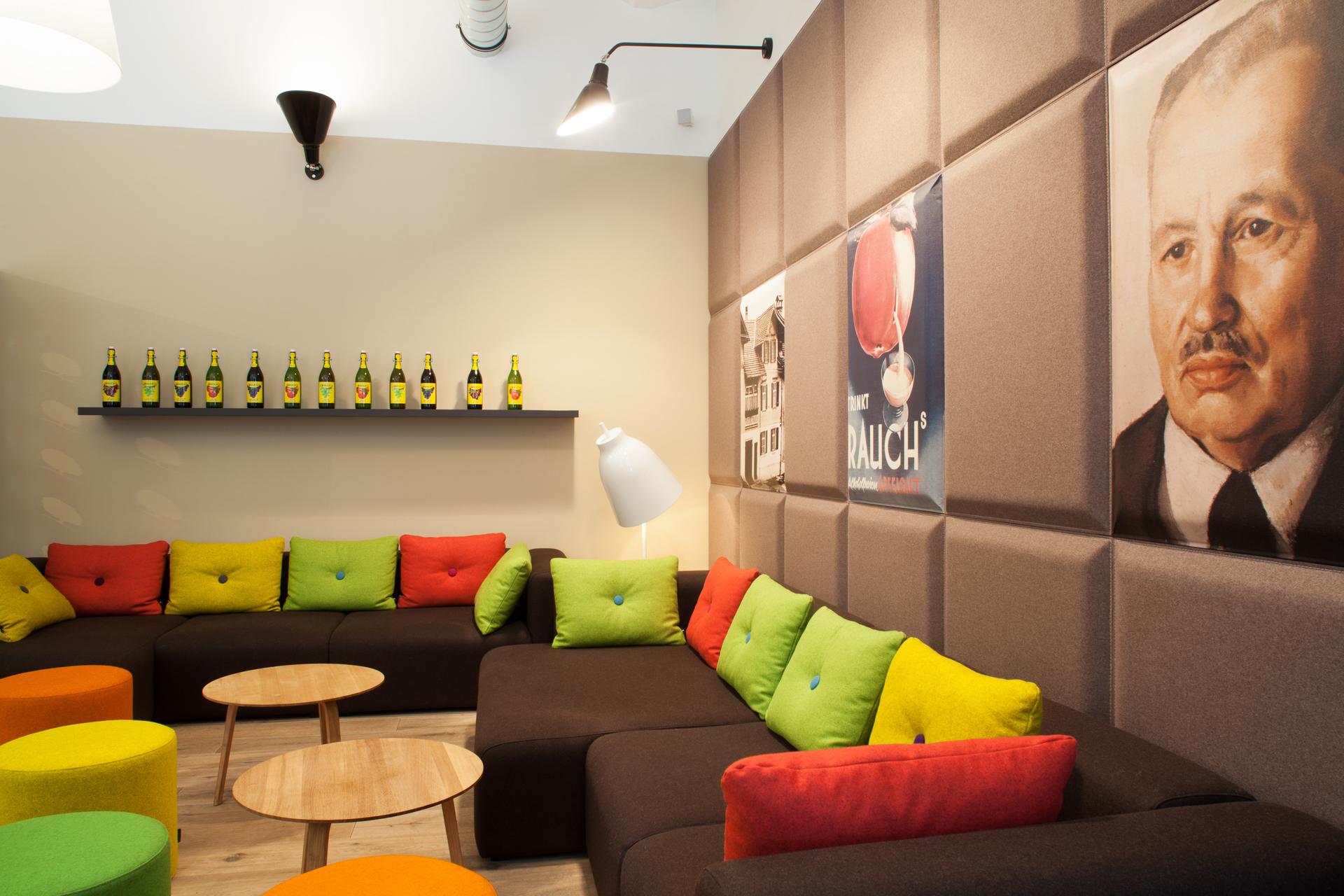 Sitzecke mit Couches, tischen und bunten Hockern in der Rauch Juice Bar