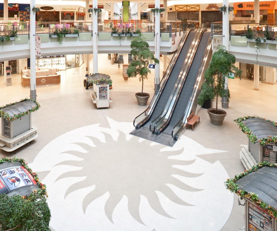 Rolltreppenbereich mit großem Sonnensymbol am Boden im Polus City Center, designed von Studio Thörnblom