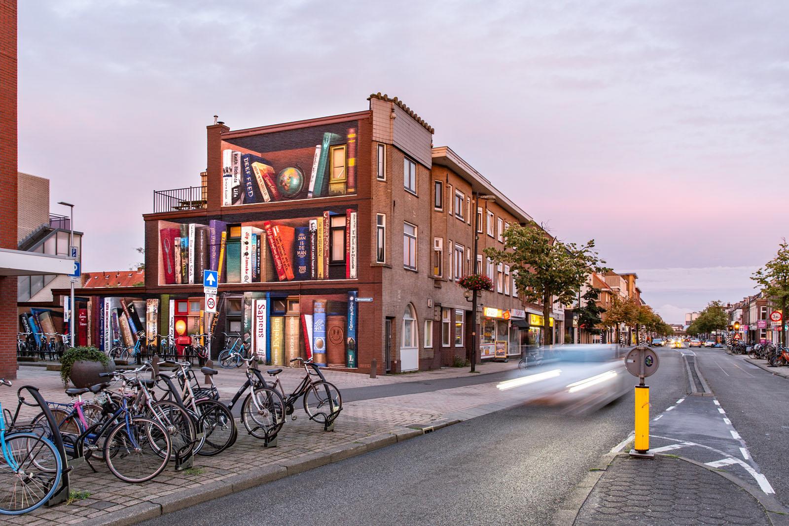 muurschildering boekenkast op zijkant gebouw Utrechtse Tweede Daalsebuurt