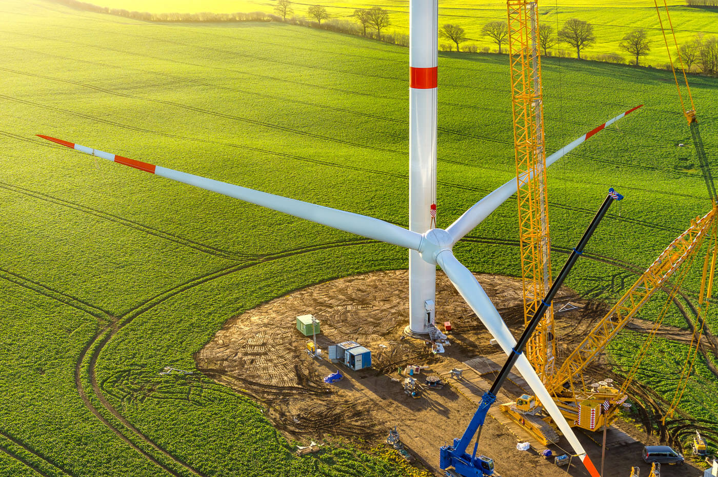 A wind turbine is constructed on a bright green field.