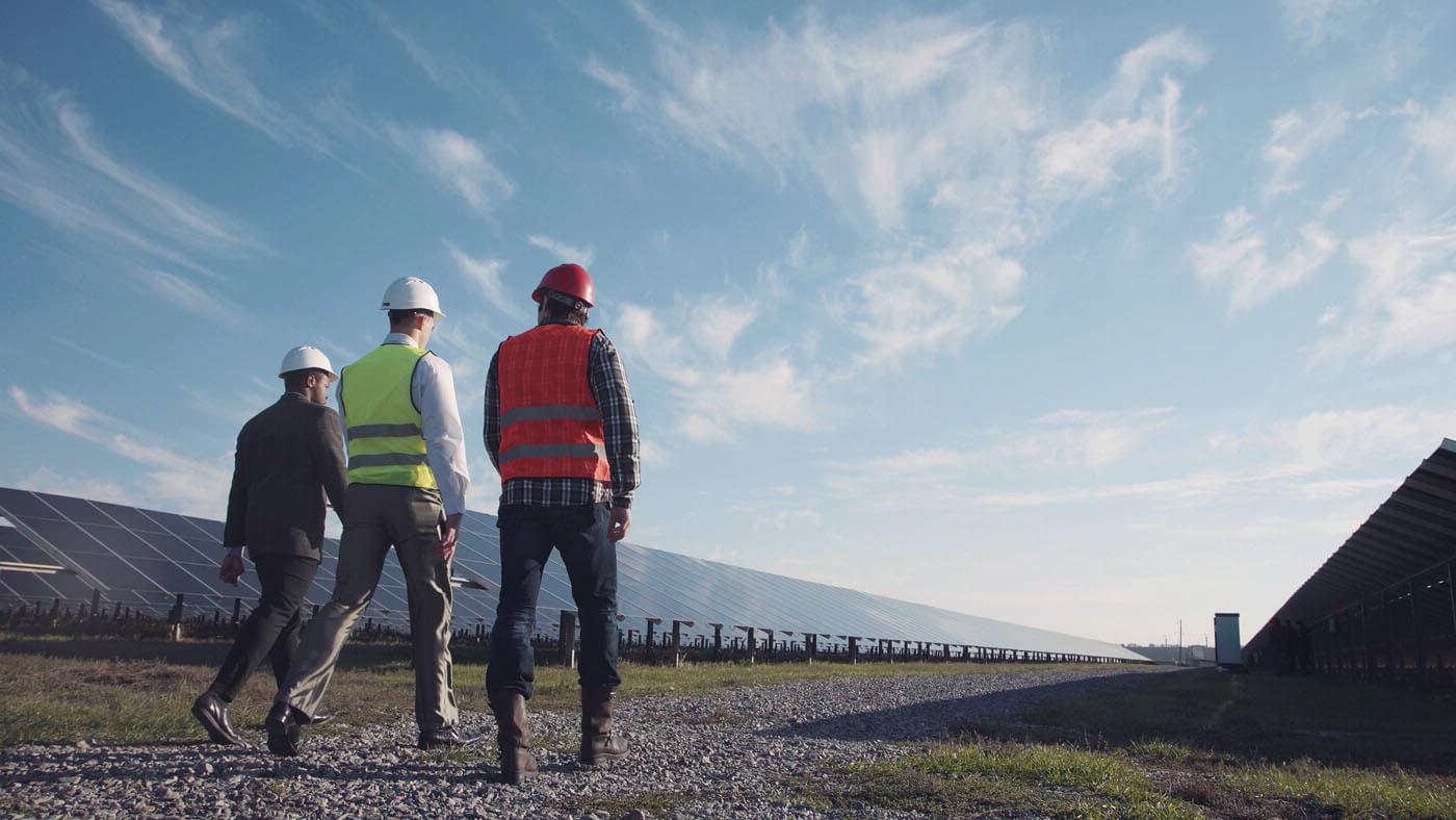 Three people in hard hats walk through a solar farm.