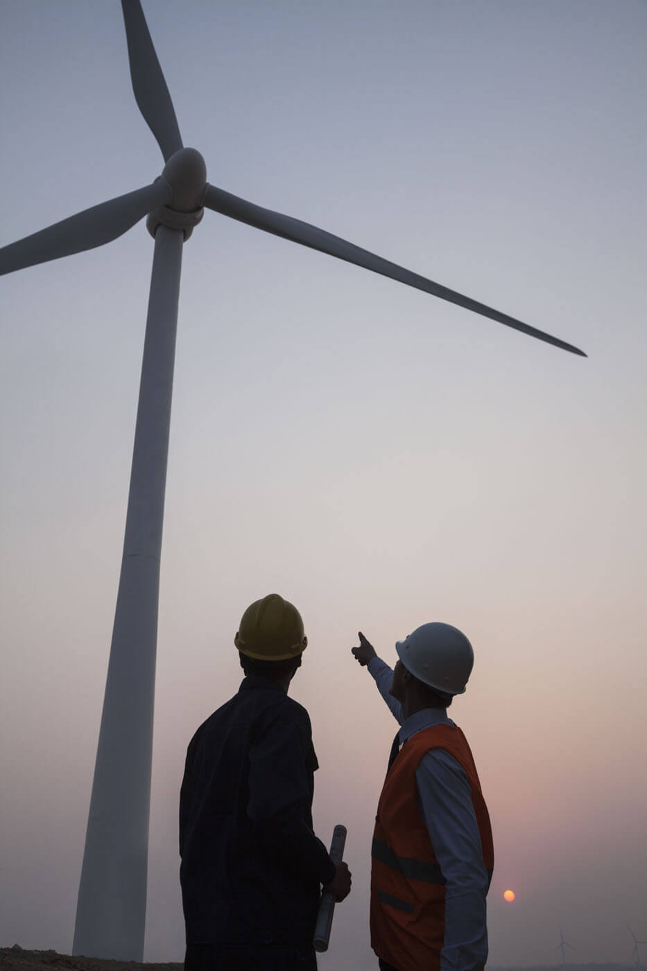 Engineers pointing at a wind turbine.