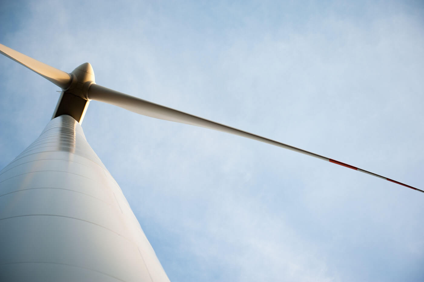 Looking up at a wind turbine against the sky.