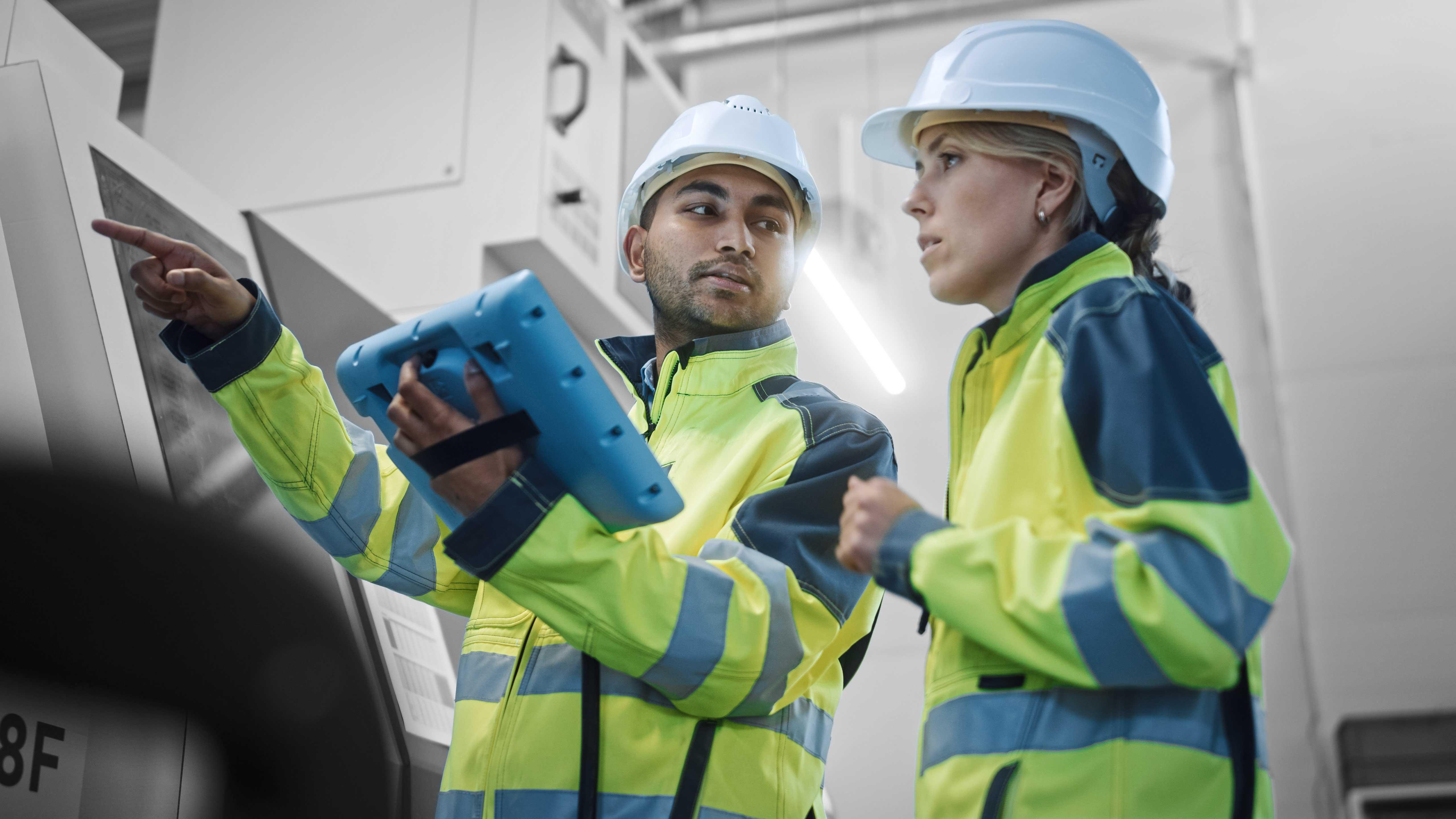 """Zwei Fachkräfte benutzen die ReAct """"Call to action"""" App im industriellen Umfeld."""