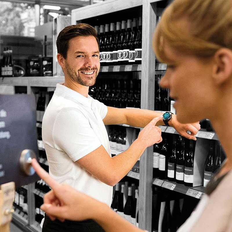 Ein Angestellter im Einzelhandel erhält eine Beratungsanfrage auf sein Smartphone – ausgelöst durch eine Service-Klingel.