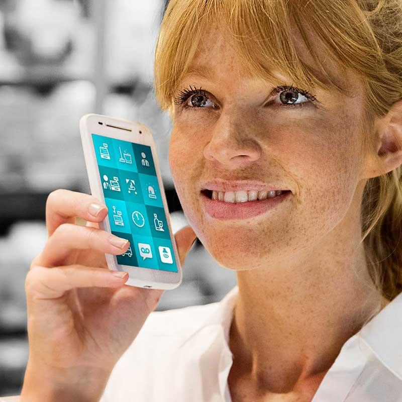 Eine Angestellte im Einzelhandel erhält eine Anfrage auf ihrem ReAct Smartphone.