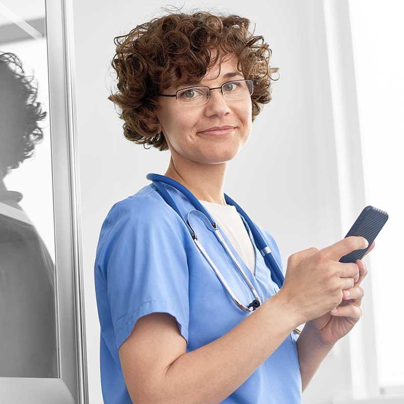 """Medizinerin mit Smartphone, auf dem die """"Call to action"""" App läuft."""