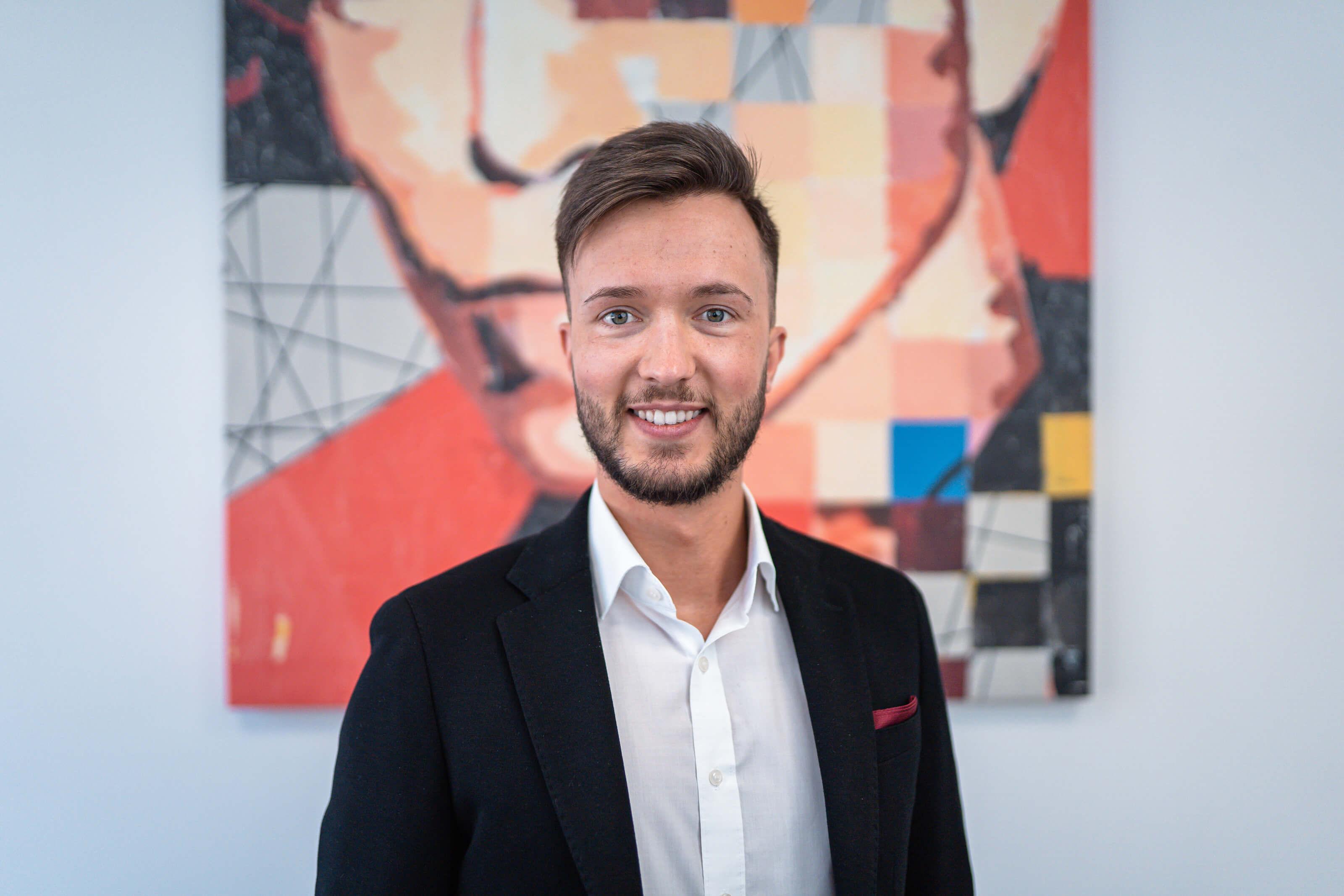 Philipp Theobald, verantwortlich für den Immobilienverkauf in den Regionen Ottweiler und St. Wendel steht im Büro vor einem bunten Kunstwerk