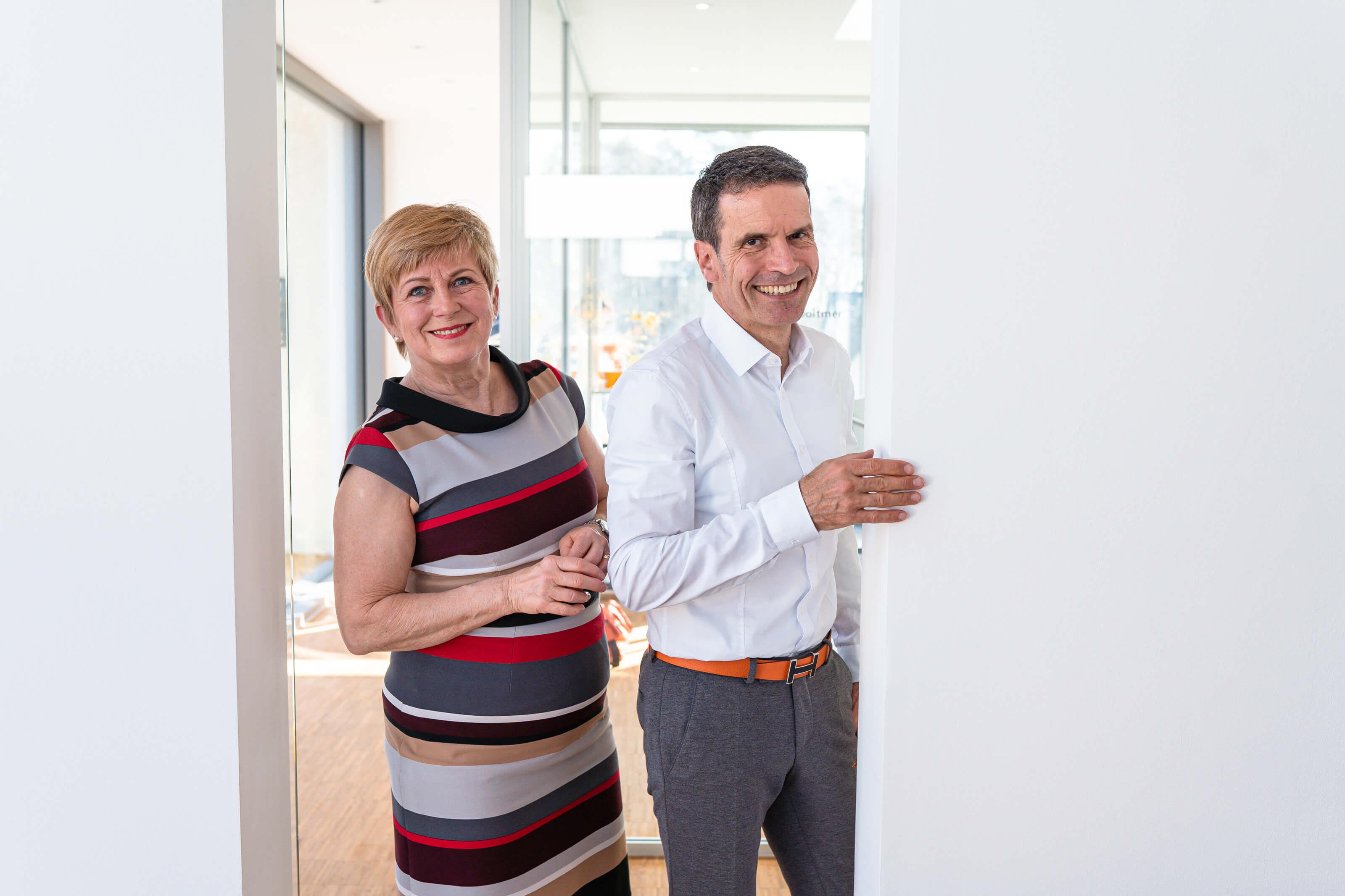 Birgit und Michael Voltmer blicken durch einen Türrahmen in die Kamera.