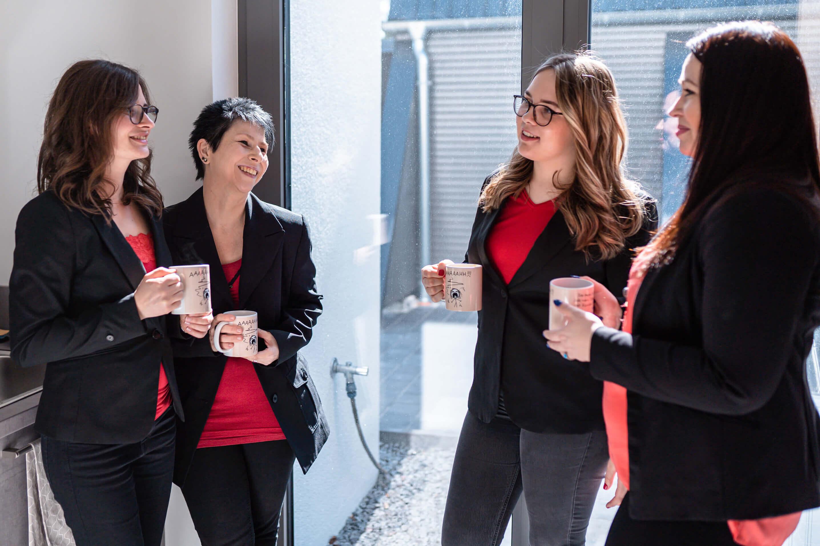 Das Team von Voltmer Immobilien trinkt zusammen einen Kaffee und lacht