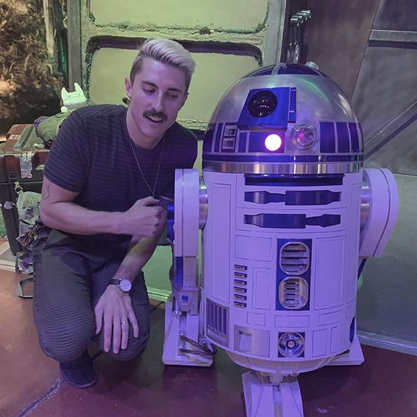 Joe Winter crouching giving R2-D2 a friendly fist bump