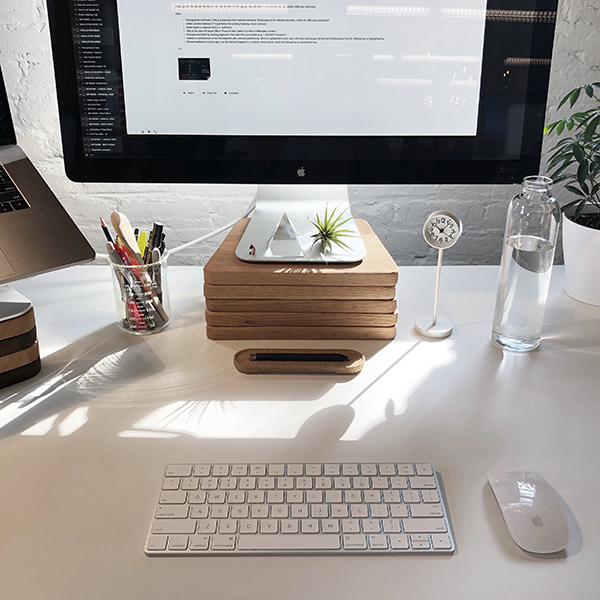 A clean, white desk with a monitor, keyboard, mouse, and pens