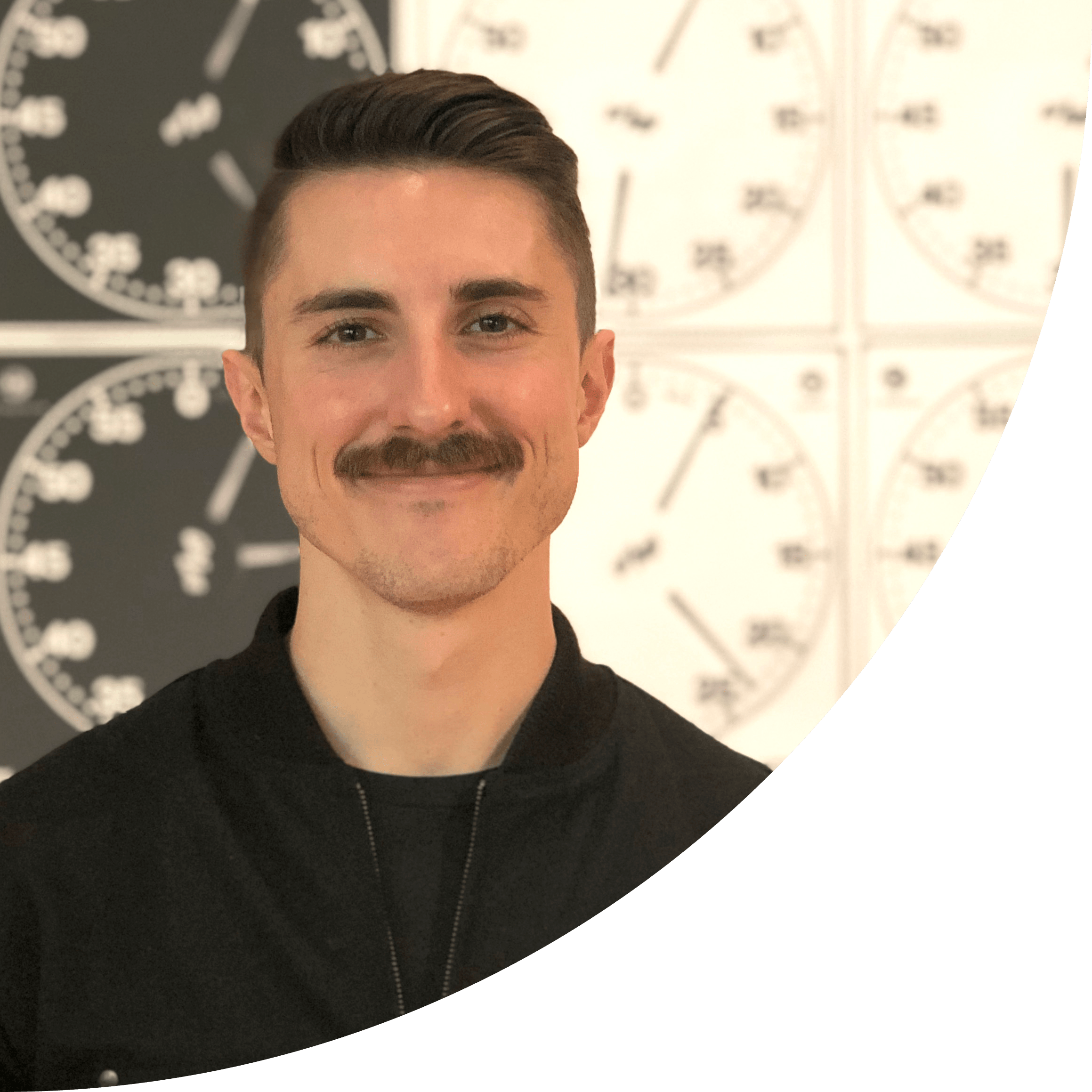 Joe Winter with a mustache smiling in front of clock photography