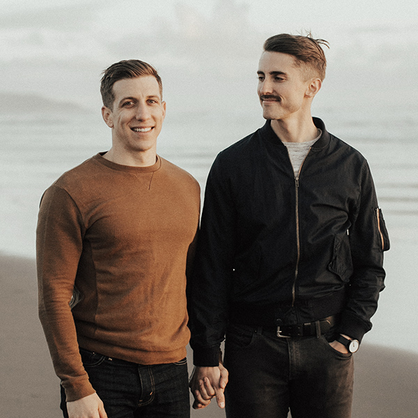 Joe Winter smiling and looking at his husband Darin at the beach